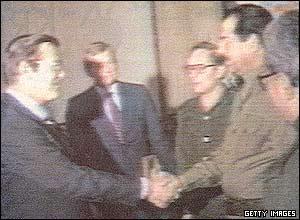 Os amigos Saddam Hussein e Donald Rumsfeld se cumprimentam