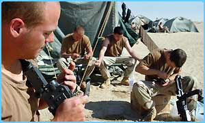 US soldiers clean their weapons in the desert of western Kuwait