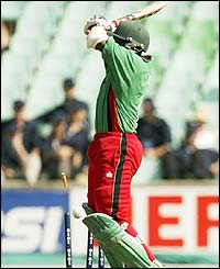 Kenya's Kennedy Otieno is hit on the elbow by a bouncer and the ball deflects on to his stumps