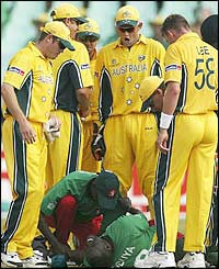 Australian players gather round Kennedy Otieno as he lies stricken after a Brett Lee bouncer