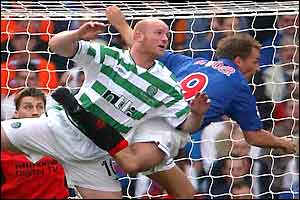 Celtic's John Hartson battles with Ronald de Boer in the air
