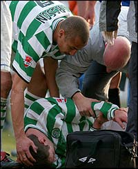 Celtic striker Henrik Larsson shows his concern as team-mate Chris Sutton lies injured