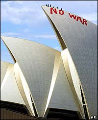 Sydney Opera House personnel inspect the slogan No War painted on the Sydney icon