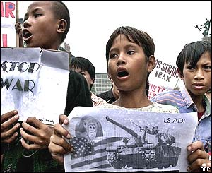 Young protesters hold anti-US posters during a demonstration in front of the British embassy in Jakarta