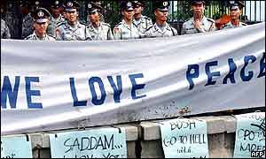 Police stand guard behind an anti-war banner during a protest in front of the US embassy in Jakarta