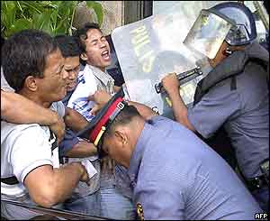 Policemen disperse Filipino protesters during an anti-US protest outside the US embassy in Manila