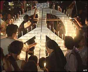 Anti-war protesters light candles on top of giant peace sign during a protest outside the US embassy in Manila