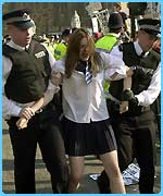 An anti-war protester's removed by police in London