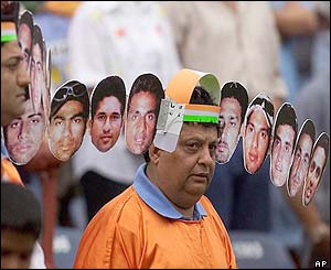 A Indian fan wears headgear bearing the faces of the of the Indian cricket team