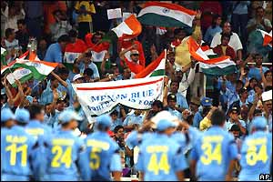 The Indian fans wave flags and celebrate as the players watch on