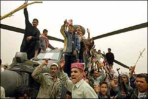 Iraqis cheer as they climb onto a US Apache helicopter Iraq says was shot down in Karbala, southern Iraq