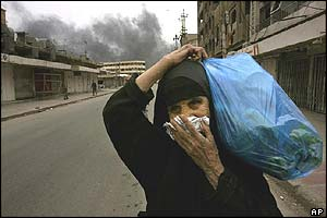 Iraqi woman covers her mouth to avoid inhaling smoke from oil fires