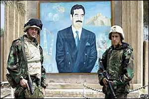 US soldiers stand either side of a portrait of Saddam Hussein in Nasiriya, southern Iraq