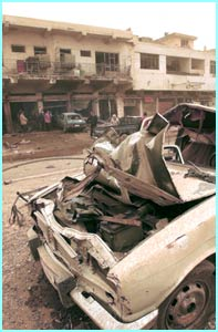 A wrecked car in a marketplace in Baghdad. The Iraqi government claim that a coalition air raid caused the damage