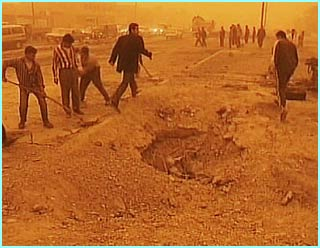 The Iraqis fill a hole caused by the attack. The air is red with sand and pollution from oil burned to confuse air raids