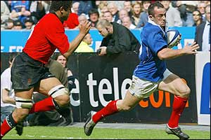 Wales's Colin Charvis tries in vain to stop Thomas Castaignede scoring for France after 27 minutes