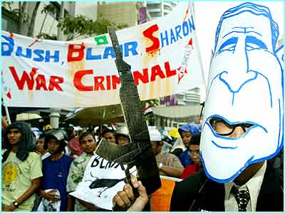 An anti-war demonstrator in Malaysia wearing a mask of President George W Bush. Protesters marched around Kuala Lumpur