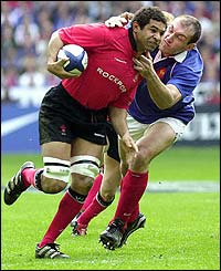 Wales' Colin Charvis is tackled by France's Olivier Brouzet