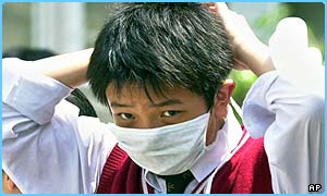 A teenage boy puts on a surgical mask for protection