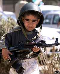 Baghdad child posing for cameras with his father's gun and helmet