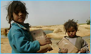 Two Iraqi children hold ready-to-eat army meals given to them by US soldiers