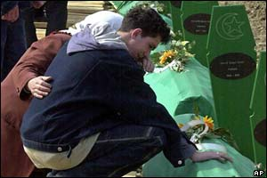 Ramo Smajic, a Bosnian Muslim refugee from Srebrenica, prays at his father's coffin