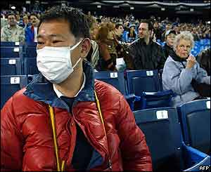 A baseball fan wears a mask to protect against SARS in Toronto's Skydome stadium.