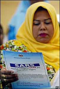 A Malaysian women reads about SARS