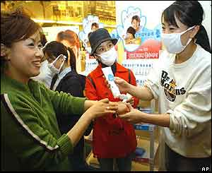 An employee of South Koreas Paru Company, right, gives a hand sanitising cream to the customers