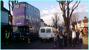 A crowd of kids (and not a few adults!) swarm round the bus