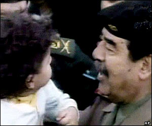 Saddam Hussein holds up a young Iraqi girl in the crowd