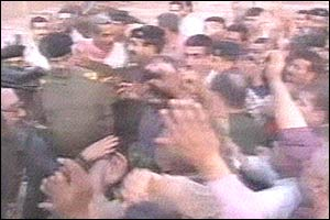 Iraqi TV shows Saddam Hussein surrounded by a crowd of cheering Iraqis