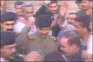 Iraqi TV picture showing Saddam Hussein raising his fist while surrounded by guards