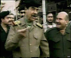 Iraqi TV shows Saddam Hussein in a Baghdad street with supporters and bodyguards