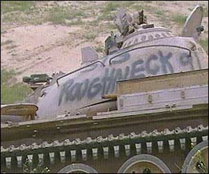 A tank with 'Roughneck' spray-painted on the side lies by the side of the road