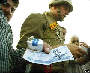 A US marine, bedecked in flowers signs autographs