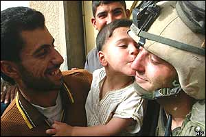 A man holds his child to kiss a US marine