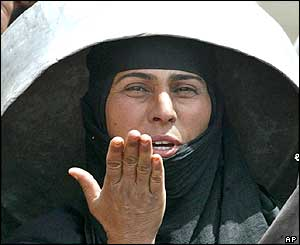 An Iraqi woman with an empty water container outside Basra
