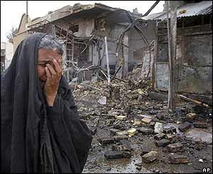 A woman cries as she walks past a bakery that was destroyed in Baghdad
