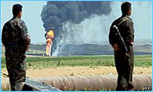 Kurds near Kirkuk, with burning oilfields in the background