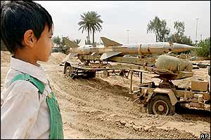 An Iraqi boy watches an abandoned SAM surface-to-air missile on its transporter truck in the al-Utefiya residential area of Baghdad, 13 April 2003