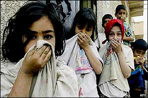 Iraqi children cover their noses from the smell as the remains of seven civilians, picked up by volunteers, are paraded through the streets of Baghdad 13 April, 2003