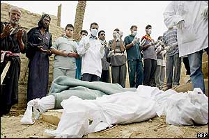 Iraqi volunteers who recovered the charred remains of civilians killed during the assault on Baghdad pray 13 April 2003 before their burial at Sheikh Maaruf-al-Karkhi cemetery