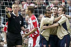 Sheff Utd's Michael Brown argues with referee Graham Poll as Arsenal celebrate take the lead
