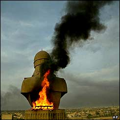 Smoke billows from the base of a sculpture of Saddam Hussein after looters set it on fire atop the rooftop of his Al-Salam Presidential Palace in Baghdad, 13 April 2003