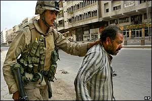 A US marine arrests a suspected looter in the streets of Baghdad, 13 April 2003