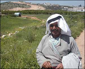 Palestinian farmer with excavation and the town of Izbat Suleiman in the background