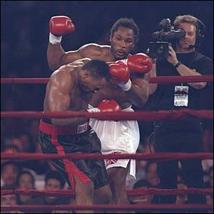 Oliver McCall stumbles as Lennox Lewis looks on during a bout at the Las Vegas Hilton in Las Vegas, Nevada. Lewis won the fight