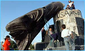 Children play with the fallen statue of Saddam Hussein in Baghdad