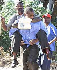 Leonard Chigwagwi is carried by a colleague after being shot in the leg